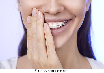 Portrait of Beautiful smiling girl covering her retainer for...