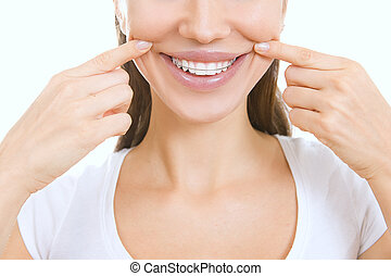 Beautiful smiling girl with retainer for teeth pointing at...