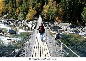 Woman on suspension bridge - Woman crossing a river on a...