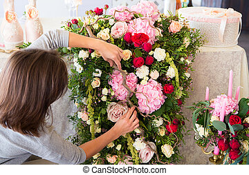 Florist at work Woman making spring floral decorations the...