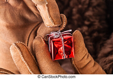 Unwrapping christmas gift - a young man wearing a sheepskin...
