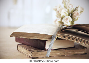 Stack of books and roses on wooden table. Shallow DOF.