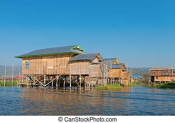 Traditional stilts house in water under blue sky -...