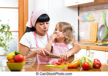 mother and daughter cooking and cutting vegetables on...