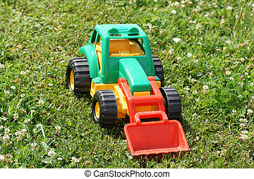 Toy green tractor on the grass.