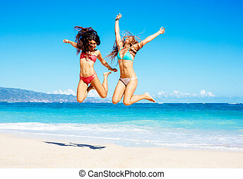 Beautiful Girls Jumping on the Beach - Two Attractive Girls...