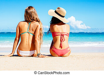 Two Beautiful Girls Sitting on the Beach - Two Attractive...