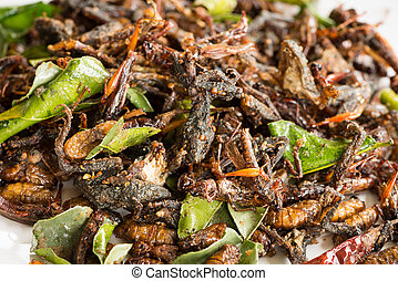 Fried edible insects mix with green lime leaves. Fried...