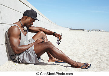Young african guy sending a text message at the beach -...