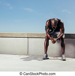 Tired young runner leaning over to catch his breath. African...