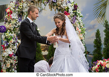 young groom and bride stand under floral wedding arch and...