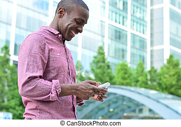 Smiling man using his cell phone - Handsome african man...