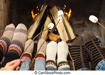 Feet warming at a fireplace with marshmallows on sticks -...