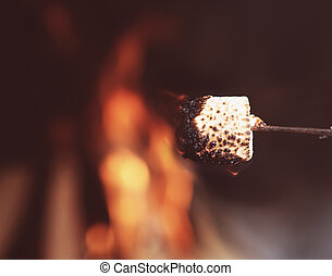 Close up of a marshmallow on a stick being roasted over a...