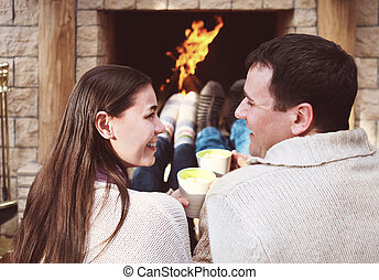 Couple holding cups with hot chocolate with marshmallows in...