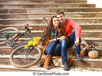 Couple with bicycle in autumn park - Happy young couple with...