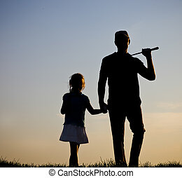 Family of a golfers at sunset - Father and his daughter...