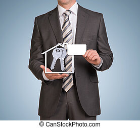 Businessman in suit hold empty card and house icon with keys...