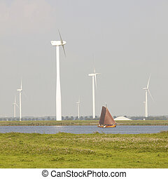 old dutch sailing vessel and modern wind turbines in The...