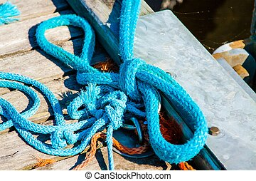 Closeup of boat cleat on a dock - old blue boat rope on dock...