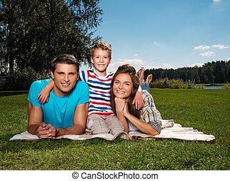 Young family with their child lying on a blanket outdoors