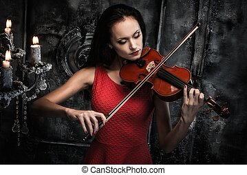 Young woman in red dress playing violin in mystic interior