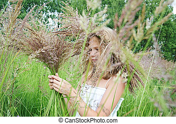 Girl in a wreath of grass with spikelets