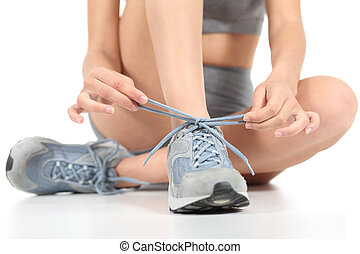 Runner fitness woman tying the shoelaces ready to sport...