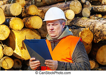Lumberjack with folder near logs in forest