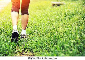 running hiking legs on green grass
