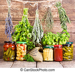 various fresh herbs and canned food on wooden background