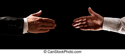 Two men reaching out to shake hands, one in a suit and the...
