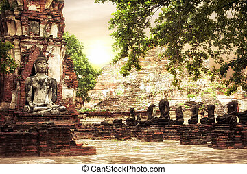 Buddha at Wat Mahathat ruins under sunset sky. Ayutthaya,...
