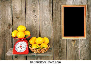 Lemons on scales and in a basket on a wooden shelf. A...