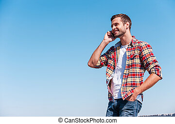 Good talk with friend. Cheerful young man talking on mobile phone and smiling while standing outdoors with blue sky as background