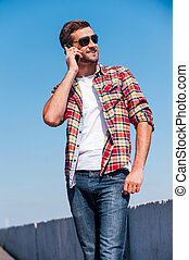 Carefree talk. Cheerful young man talking on mobile phone and smiling while standing outdoors with blue sky as background