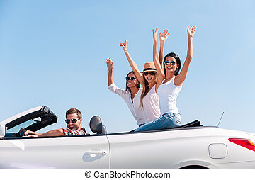 Spending great time together. Group of young happy people enjoying road trip in their white convertible while girls raising arms and smiling