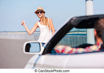 Hitching a ride. Beautiful young funky woman hitch-hiking on...