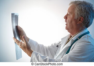 Checking x-ray - Doctor checking with surprise x-ray of a...
