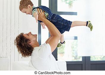 dad and young boy - man sitting on sofa and lifting up his...