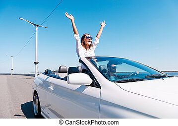 Couple in cabriolet Happy young couple enjoying road trip in...