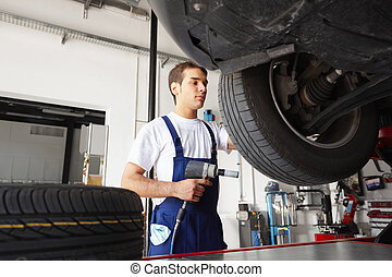 mechanic replacing car tyre in auto repair shop Low angle...