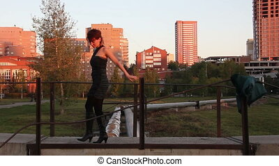 Red-haired woman wearing black dress and black boots posing...