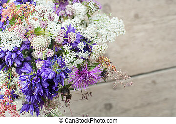 Beautiful tender bouquet of summer meadow flowers on wooden...