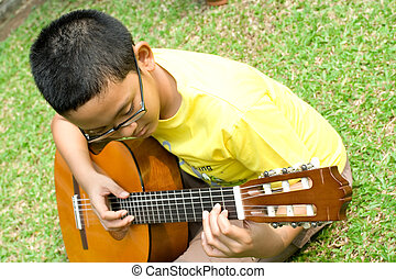 ethnic boy play guitar - asian ethnic boy enjoy playing a...