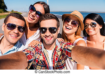 Capturing fun. Five young happy people making selfie and...