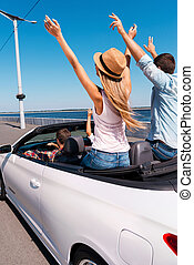 Traveling with fun. Rear view of young happy people enjoying road trip in their convertible and raising their arms up