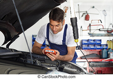 mechanic leaning on bonnet with tester equipment