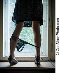 Woman legs on the window with a lowered Slip