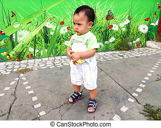 Baby - Naughty baby boy stands on a playground at summer day